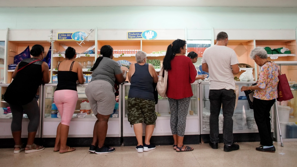 Cubanos esperan a ser atendidos en una tienda.