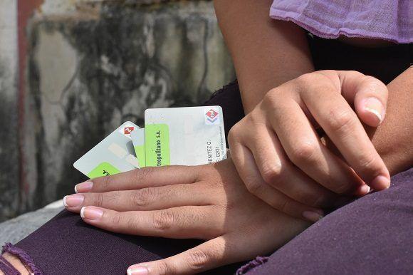 Una mujer sostiene tarjetas emitidas por el Banco Metropolitano de Cuba.