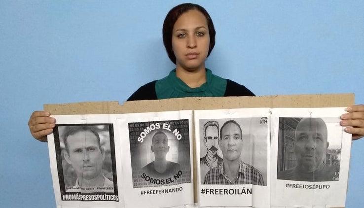 Nelva Ortega, esposa de José Daniel Ferrer, con las fotos de los cuatro detenidos.