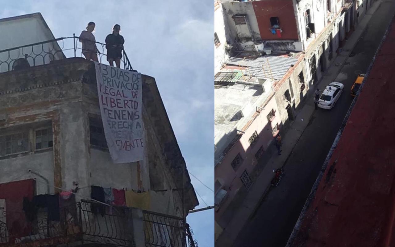 Katherine Bisquer y Camila Lobón colocan un cartel en protesta por la vigilancia policial.