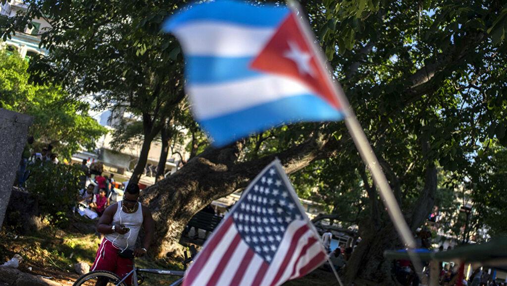 Una bandera cubana y estadounidense en un parque wifi de La Habana.