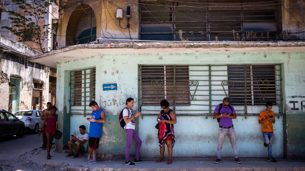 Cubanos conectados a internet en la calle.