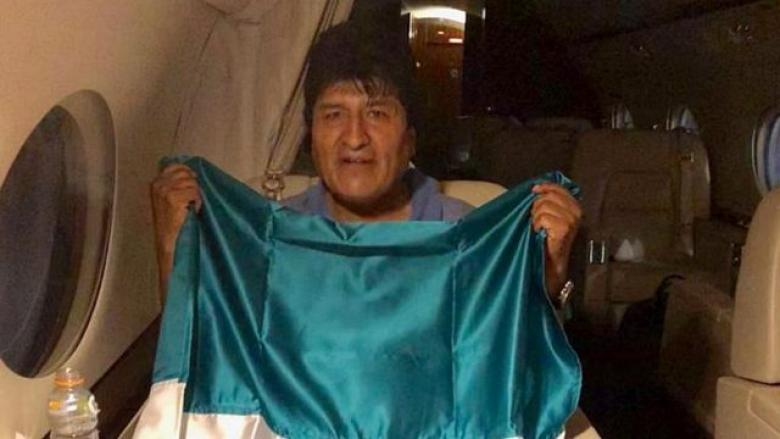 Evo Morales con una bandera mexicana en el avión que lo llevara a México.